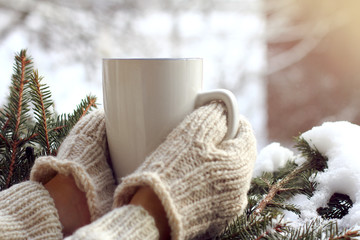 warming drink for winter morning/ Hands in mittens are holding white mug against the background of snow-covered green tree
