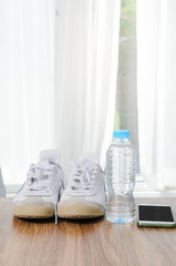 Sport shoes a bottle of water and smart phone on wooden floor, sport lifestyle concept.