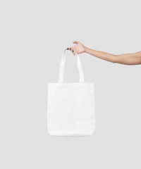 hand holding bag canvas fabric for mockup blank template isolated on gray background.