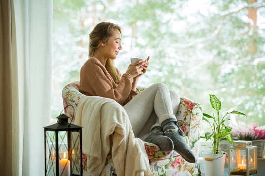 Young woman sitting home in a chair by the window with cup of hot coffee wearing knitted warm sweater. Cozy room decorated with lanterns and candles. Scenic view of pine trees in snow in window