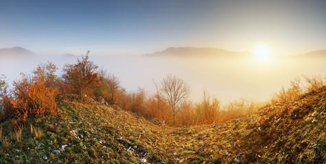 Fototapete - Sun over clouds mist in mountain landcape at sunrise
