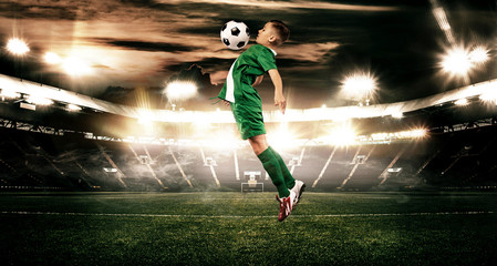 Kid - soccer player. Boy forward in football sportswear on stadium with ball. Sport concept.
