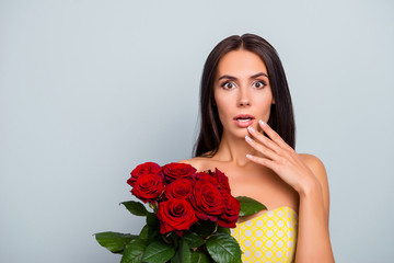 Wow unbelievable! Unexpected declaration of love, getting flowers from secret admirer, lover. Shocked beautiful woman is holding nice roses, wearing dotted yellow dress, isolated on grey background
