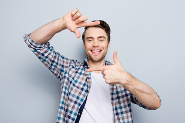 Closeup of young, attractive, happy, creative, cheerful guy making frame with fingers in front of face, looking at camera  over grey background