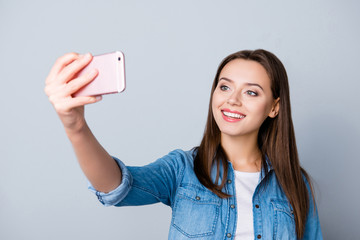 Young, smiling, cute, pretty girl having video-call with good internet speed, standing over grey background