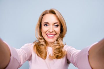 Close up portrait of cheerful happy joyful with toothy beaming smile mature woman wearing light pink blouse she is having a video connection via internet and her smartphone isolated on grey background