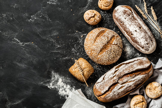 Bakery - rustic crusty loaves of bread and buns on black