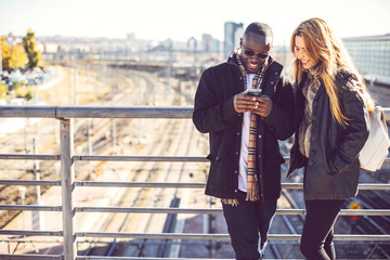 Laughing businesspeople sharing phone outside