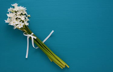 White narcissi, tied with ribbon on a blue background