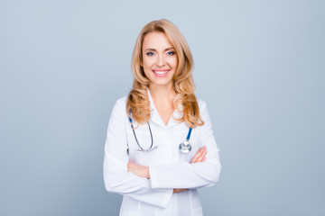 Portrait of confident with toothy beaming smile qualified experienced clever intelligent doctor wearing white formal wear she is standing with crossed folded arms, isolated on grey background