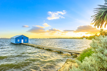 Blue Boat House: the iconic and most photographed Perth landmark in Western Australia. Scenic sunset landscape on the Swan River. Boathause with wooden jetty and copy space.