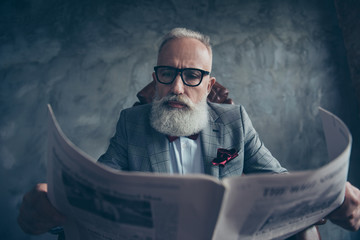 Attractive, smart, cool, old businessman in glasses and jacket reading newspaper, news about politic, bitcoin, finance, economy, science over gray background, sitting in chair