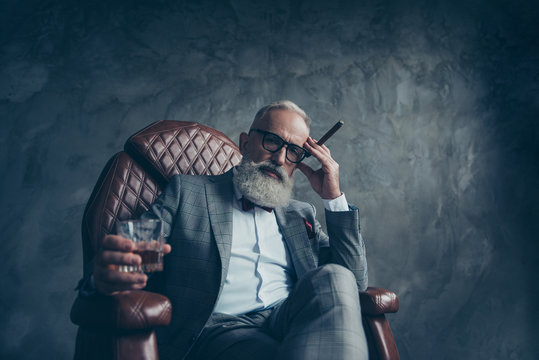Minded, ponder, dreamy gentlemen,  selective, bearded investor in glasses, hold cigarette and glass with cognac, in tux, jacket, sit in leather chair over gray background, work place, station