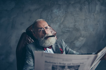 Handsome, attractive rich old man in glasses with cigarette in mouth, hold newspaper, looking at camera with one close eye, shares stock, news, workstation, sit in leather chair over gray background
