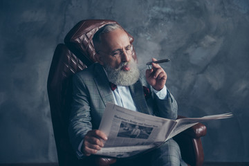Portrait of brutal harsh old man in tuxedo holding, reading, looking at newspaper, smoking cigar, sitting in leather armchair, shares, money, stock, economy, finance, gray background