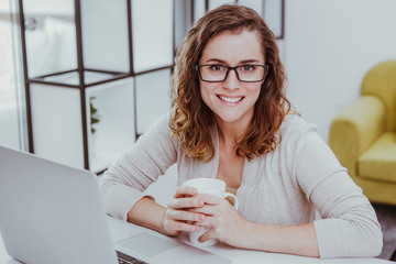 Woman Working on Laptop and Drinking Tea at Home