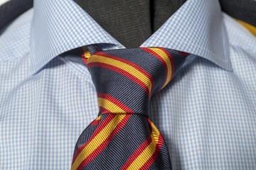 halber englischer knoten in einer Krawatte auf einem blauen Hemd zu einem tweedjaket