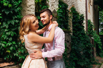 girl laughing and hugging her boyfriend in a pink shirt and wooden bow tie against a background building with bushes