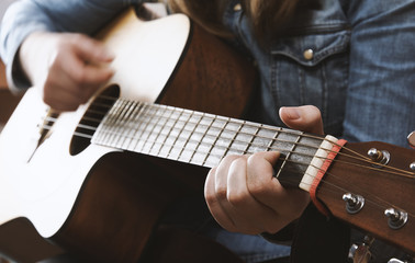 Young girl playing acoustic guitar with jeans shirt