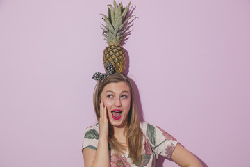 Young beautiful smiling woman holding pineapple on head. Summer fruit concept.