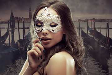 Beautiful brunette with Venetian mask. Young and beautiful woman on Venetian view background, gondolas.