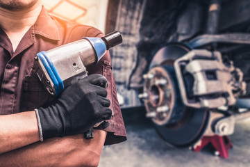The abstract image of the technician hold a air wrench and blurred disc brake is backdrop. the concept of automotive, repairing, mechanical, vehicle and technology.
