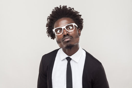 Portrait choke man in white glasses grimacing at camera.