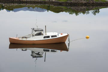 yellow boat reflected on a fjord in Ringstad at Lofoten Island in Norway