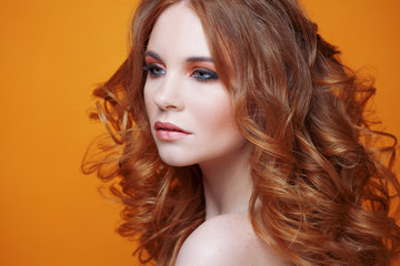 Beautiful redheaded girl with luxurious curly hair. Studio portrait on yellow background. Excellent hair