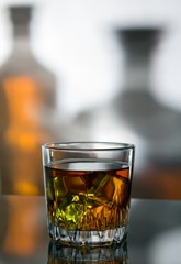 a glass of whiskey with ice against the background of bottles