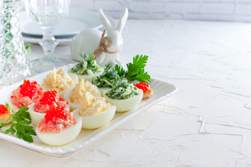 Festive decoration variants of stuffed eggs - red (red fish, caviar), yellow (cheese, eggs) and green (fresh cucumber, dill) on a white dish, horizontal, copy space