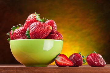 Strawberries in the bowl on wooden table.