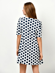 Young beautiful woman posing in new casual black and white dotted dress