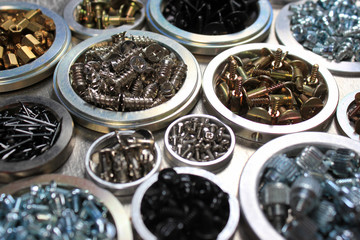 Screws, bolts and nuts on metal background