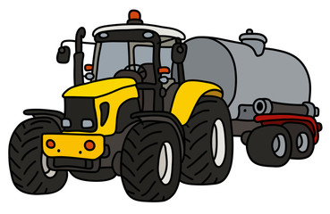The yellow heavy tractor with a steel tank trailer