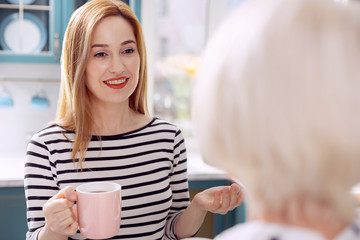 Sharing thoughts. The focus being on a pretty young woman talking to her elderly mother and smiling at her fondly while telling about her day and drinking coffee