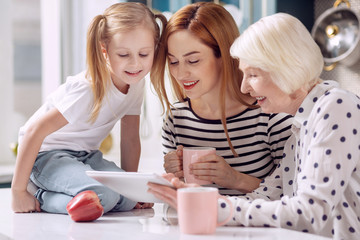 Contemporary digitalization. Cute little girl sitting on the kitchen counter and watching a video on laptop together with her mother and grandmother drinking coffee