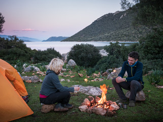 couple camping with campfire and tent outdoors