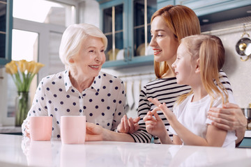 Precious wisdom. Charming elderly woman sitting at the kitchen counter with her daughter and granddaughter, drinking coffee and sharing her experience with her beloved girls