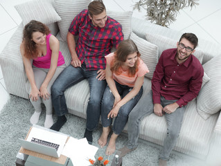 triumphant group of friends laughing while sitting on the couch in the living room