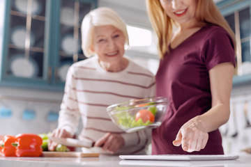 Helpful device. The focus being on the hand of a pleasant young woman checking a recipe on the tablet while making a salad with her elderly mother Wall mural