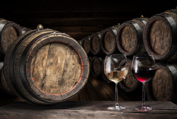 Wine barrel  and two wine glasses on the old wooden table.