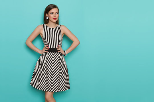 Beautiful Young Woman In Black And White Striped Dress Is Looking Away