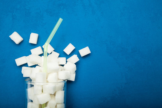 Spilled sugar from a glass on a blue background. Giant sugar concentration in everyday beverages.