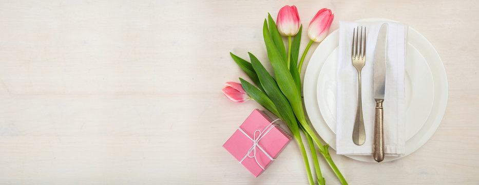 Valentines day table setting with pink tulips and a gift on white wooden background. Top view, copy space, banner