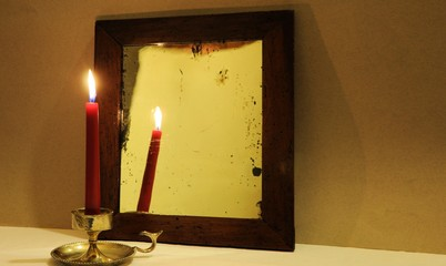 Red candle reflected in old mirror