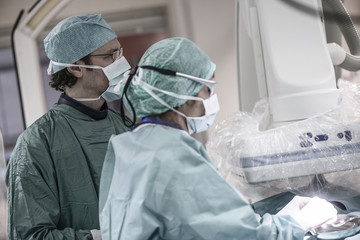 Neuroradiologist with assistant in scrubs