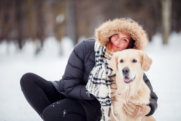 Photo of smiling woman squatting next to labrador in winter