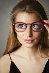 Beautiful big blue eyes through glasses, studio