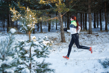Image of young female athlete running through winter forest